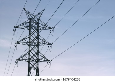 Power line against the blue sky. Energy, electricity, communication. High-voltage tower, line