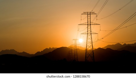Power Line High Voltage Electricity Pylons at Sunset
