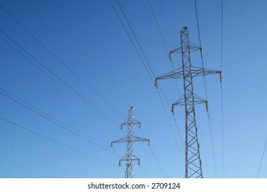 Power Line. High Voltage Transmission Tower on Blue Sky.