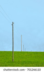 Power line on a hayfield against a blue sky.