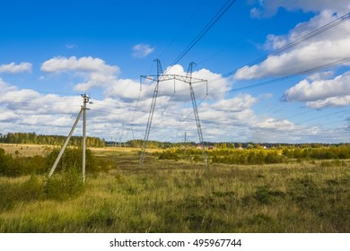 Power line and panorama of autumn forest and field on a sunny day with clouds.