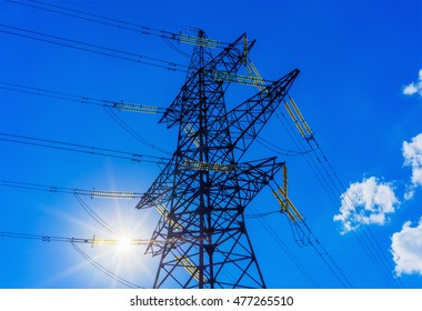 power line silhouette against the blue sky with rays of sunlight