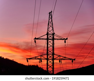 Power line support in the mountains at sunset