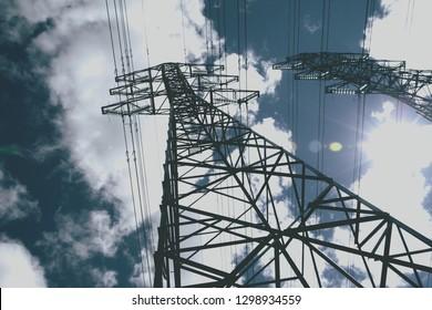power line towers against blue sky, vintage color effect