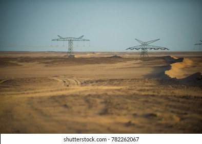Power line towers in desert on blue sky background. Electricity distribution stations. Electric energy transmission. Global warming, climate change. Ecology, eco power, technology concept.