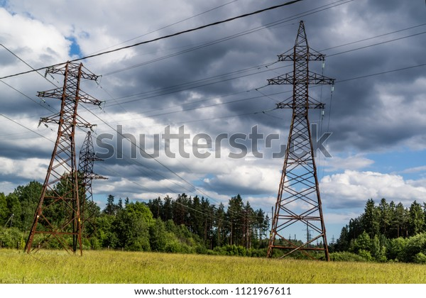 Power line towers and wires in greenery. Sunny day.