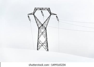Power line in winter, big, high voltage pylon on minimalist, snowy mountain landscape