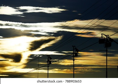 Power lines against golden shiny clouds at dusk