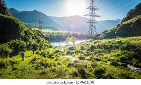 Power lines in the beautiful mountain landscape with a water stream in Altai, Siberia, Russia.
