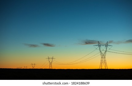 power lines being lit up in the dusk sky