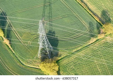 Power lines crossing farmland seen from the air in early morning. Controversial for spoiling views across the countryside. Essex, England.
