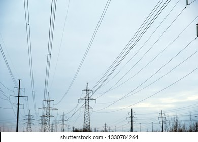 Power lines with lots of wires and metal supports on open water on sky background in spring