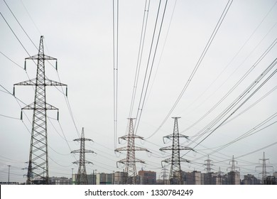 Power lines with many wires and metal supports on the open water against the sky. The concept of a modern city in the background and a lot of electrical wires in the foreground