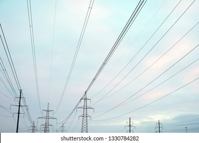 Power lines with many wires and metal supports on the open water against the sky