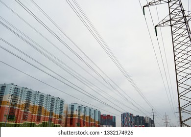 Power lines with many wires and metal supports against the sky. The concept of a modern city and a lot of electrical wires. Positive multicolored houses in a modern European residential area