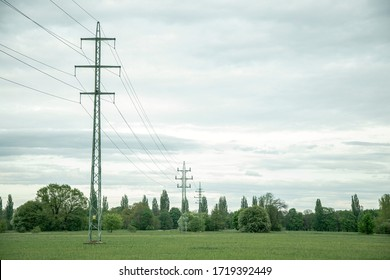 power lines in a natural landscape with trees and sky