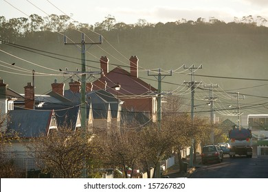 Power Lines running through a suburban street beautifully backlit by the early morning sun