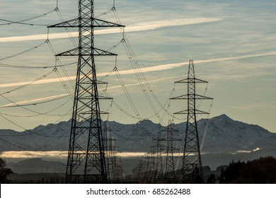 Power lines with snowy mountains in the background.