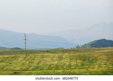 Power lines and summer hills of Caucasus foothills