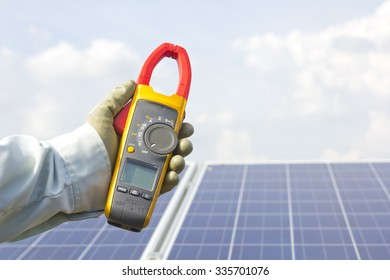 Power meter on hand, solar panel background