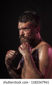 Power, might, magic. Man in fight position with blood paint on face, fists. Bearded hipster with tattoo on chest skin on black background. Sport, boxing, fighting. Halloween, holidays celebration