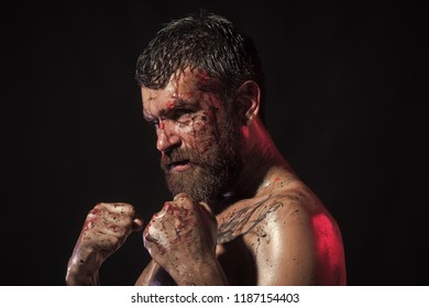 Power, might, magic. Man in fight position with blood paint on face, fists. Sport, boxing, fighting. Bearded hipster with tattoo on chest skin on black background. Halloween, holidays celebration.