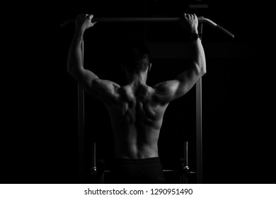 Power muscular bodybuilder guy doing pullups in gym black and white photo