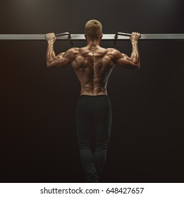 Power muscular bodybuilder guy doing pullups in gym. Fitness man pumping up lats muscles. Fitness and bodybuilding training health lifestyle concept