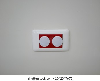Power outlet in a hospital patient room with electrical outlet safety covers/caps on it preventing a baby from electric shock and electrocution