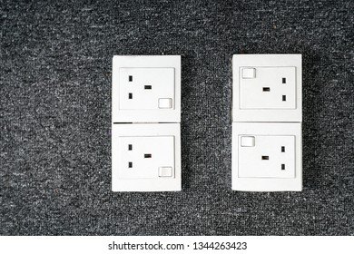 Power outlet on a grey color carpeted floor