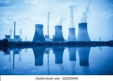 power plant with cooling towers and reflection in the river
