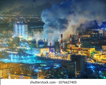 Power plant emitting smoke from smokestacks over night city skyline. Moscow, Russia