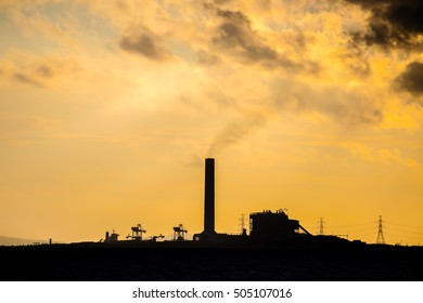 Power plant factory silhouette over sunset at sea