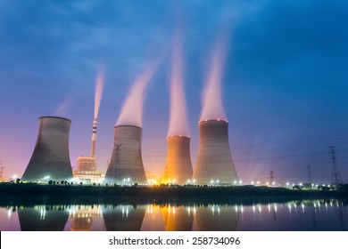 power plant at night , cooling tower closeup with steam