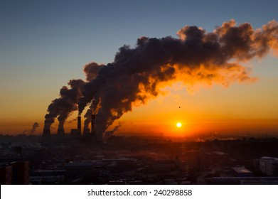 Power plant pipes with swirling smoke at sunrise. Environmental pollution. View against the sun.