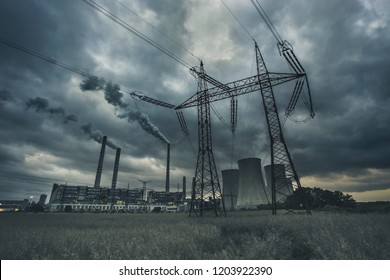 "Power plant ""Pocerady"" with high voltage power line, pylon, chimneys and cooling towers with dramatic clouds in the evening"