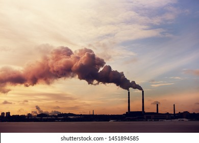 Power plant silhouette in the winter at sunset. View of pipes with smoke after burning coal.