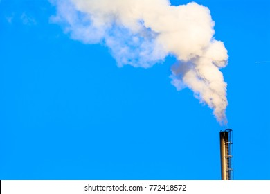 Power plant smokestack with carbon emission - co2, dioxide or fossil fuel. Air pollution by industry. Chimney and smoke cloud on blue sky background.