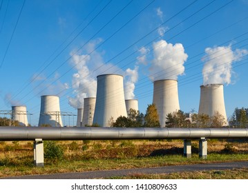 Power plant smoking chimney at sunset, environmental pollution concept.