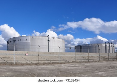 Power plant storage towers against cloudy blue sky