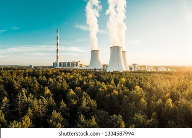 A Power plant with white smoke over it's chimneys