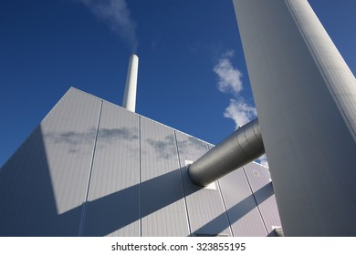 Power plant at work. Light steam coming from chimneys. Clear blue sky.