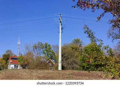 power pole and cable at autumn in germany rural countryside on sunny afternoon with blue sky