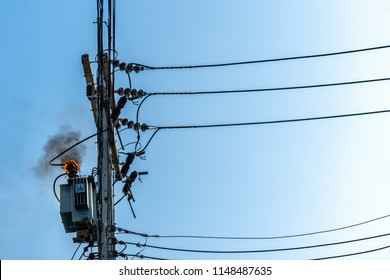power pylon overload or electric short circuit at transformer on poles and fire or flame with smoke on blue sky