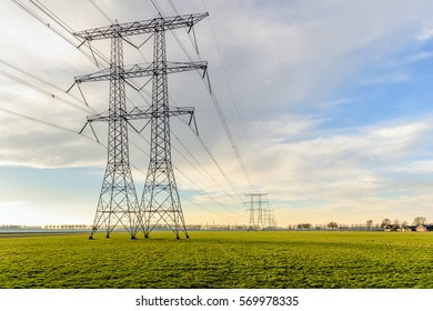Power pylons and high voltage lines in an agricultural landscape in the Netherlands. In the background is the edge of a small village. It is a cloudy day in the winter season.