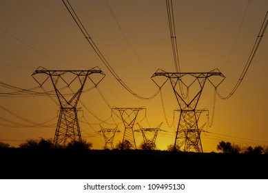 Power pylons with the sun setting on the background