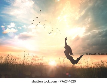 The power of releasing judgment concept: Silhouette of a woman jumping and broken chains at sunset meadow with her hands raised