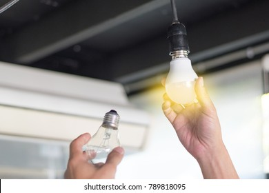 Power saving concept. Asia man changing compact-fluorescent (CFL) bulbs with new LED light bulb.