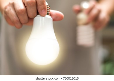Power saving concept. Hands holding  new  Light Emitting Diode ( LED ) light bulb with light on and blur spiral compact-fluorescent (CFL) bulbs behind for copyspace.