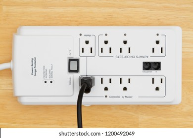A  power saving surge protector on wood with power cord